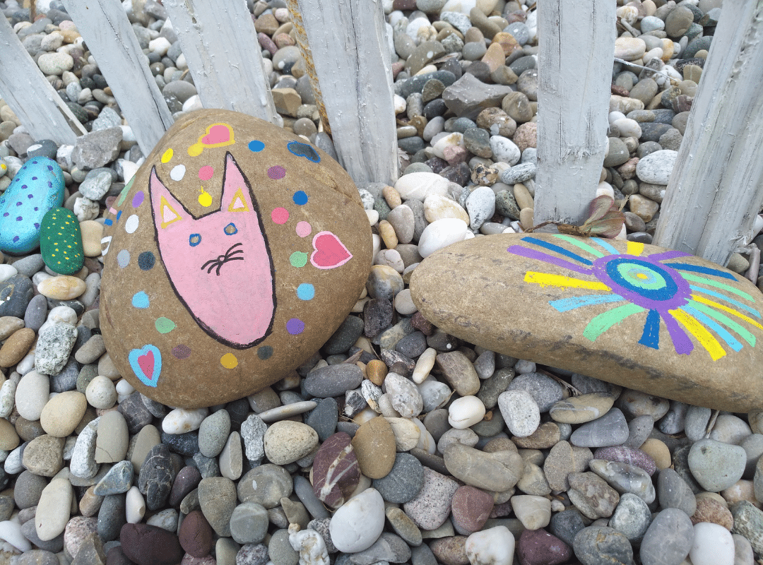painted cat stone and sun stone on the ground