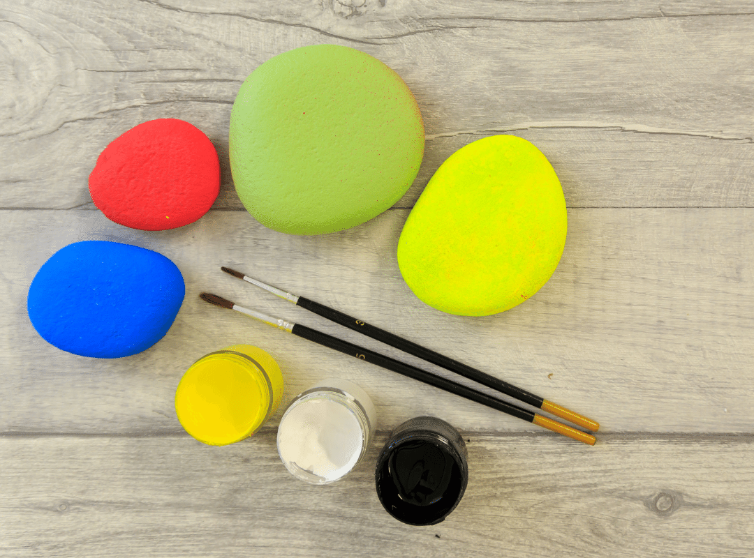 base painted rocks in yellow, green red and blue paint